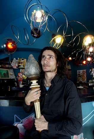 Salgueiro, con la lámpara-antorcha de la tienda de su padre, en el bar Augamar de Vilariño, que diseñó él