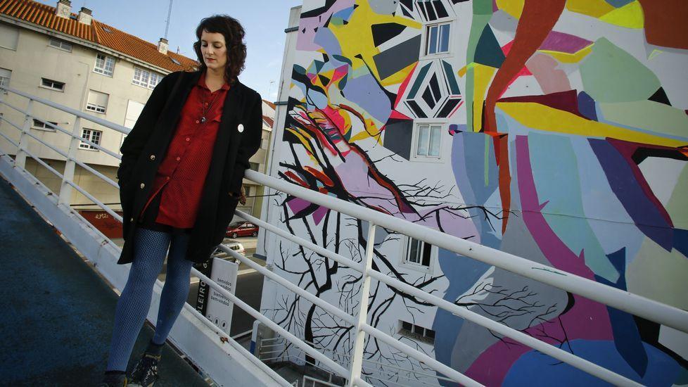 Paula Fraile, junto al mural que realizó en una vivienda próxima al punte de A Pasaxe