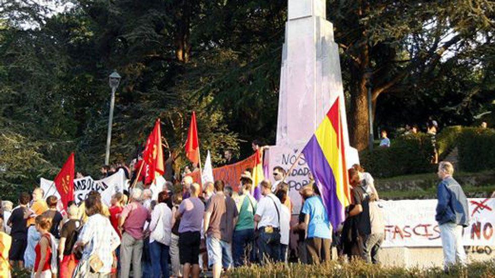 Manifestantes protestan frente a una cruz franquista.