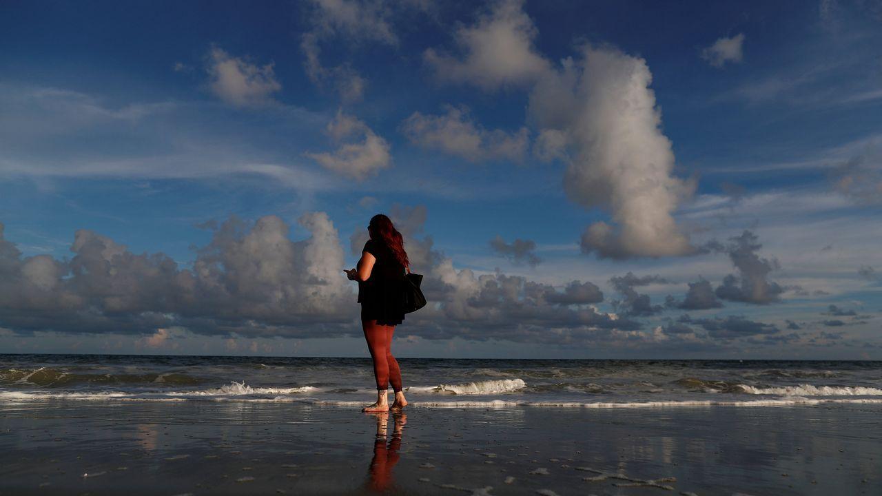 Una mujer pasea por la playa de Myrtle.