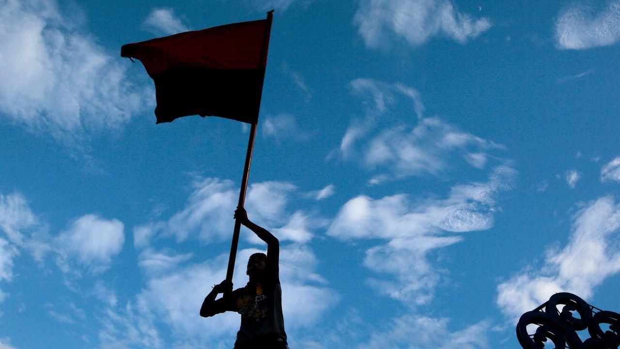 .Un partidario del presidente de Nicaragua, Daniel Ortega, sostiene una bandera sandinista durante una manifestación en Managua