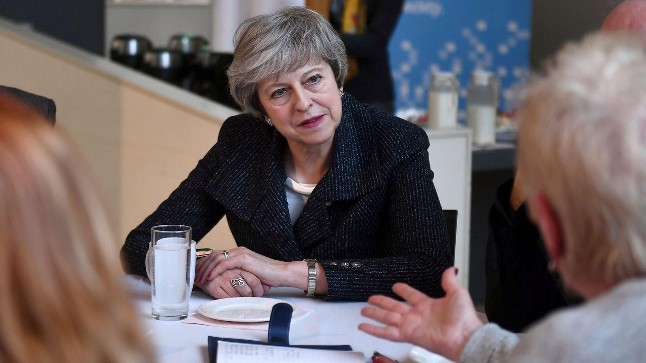 Theresa May ofrece su dimisión a cambio de que se apruebe su plan del «brexit».Theresa May, durante su vista a un centro comunitario de Belfast