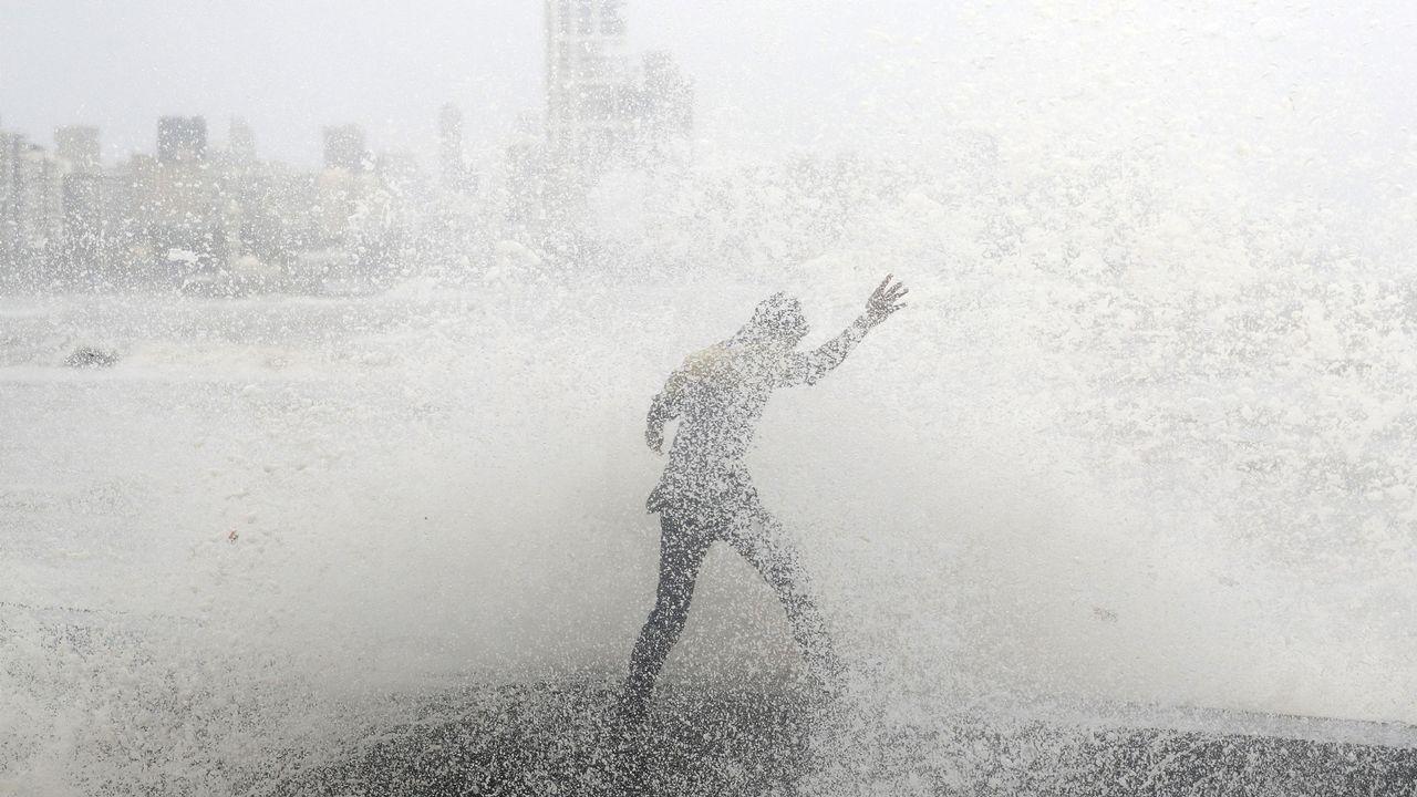 Un hombre pierde el equilibrio cuando se empapa con una gran ola durante la marea alta en un paseo marítimo en Mumbai, India