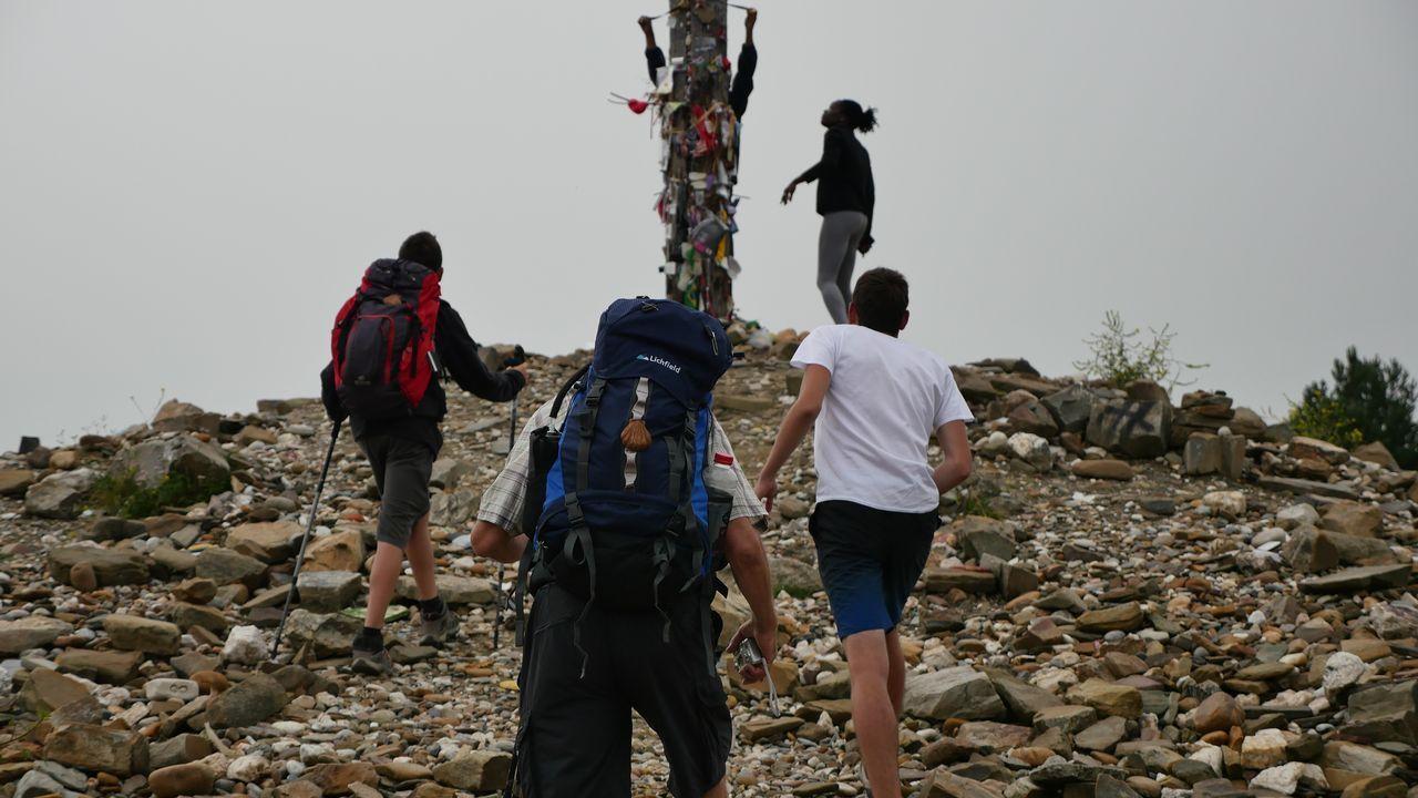 Varios peregrinos caminan junto a la cruz de Fierro