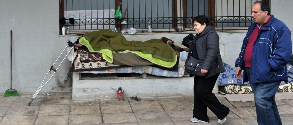 Syriza se hace con el poder en Grecia.Dos personas con la vista en el suelo caminan por una calle donde descansa un sintecho en la ciudad de Salónica.