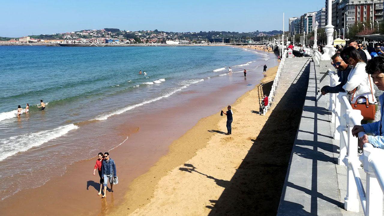 La playa de San Lorenzo de Gijón, con paseantes, espectadores y bañistas en pleno Sábado Santo