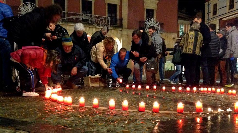 ¡Búscate entre las más de 100 fotos de la cena organizada por Renacer en Ribeira!.Varias personas encienden velas por las víctimas del VIH en la plaza Mayor de Gijón