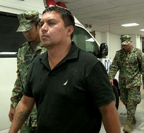 Treviño camina sin esposas, tras su detención, entre militares.