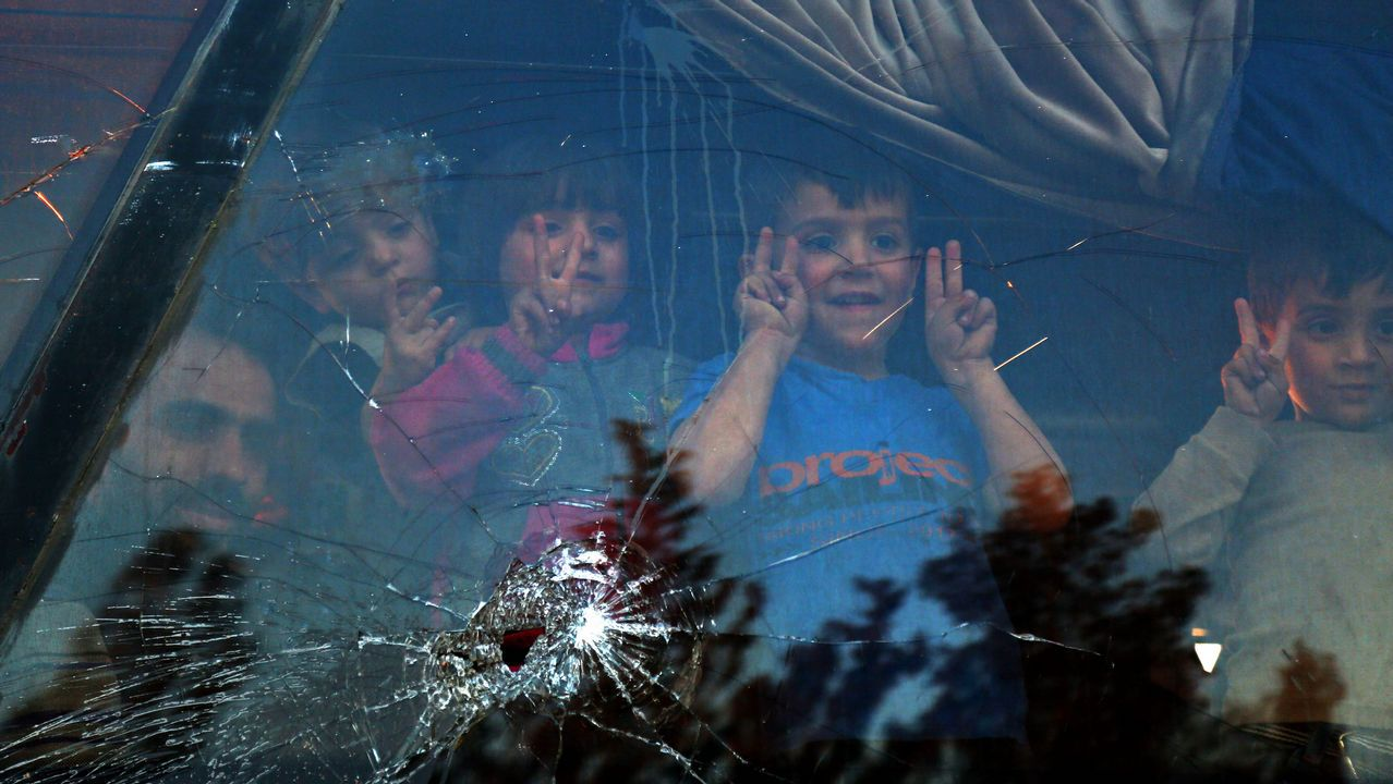 Un grupo de niños sirios saludan desde el interior de un autobús en la localidad siria de Al-Bad