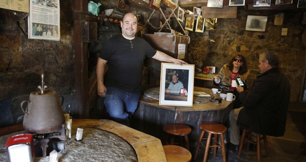 .José Luis Goldar Díaz, ayer, con una foto de su padre en la taberna O Muíño de Caldas, situada a orillas del río Umia.