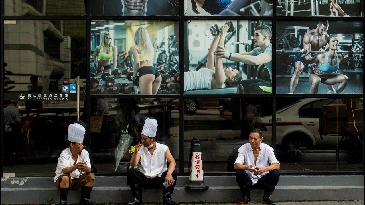 Tres cocineros descansan frente a un gimnasio en el centro de Shanghái