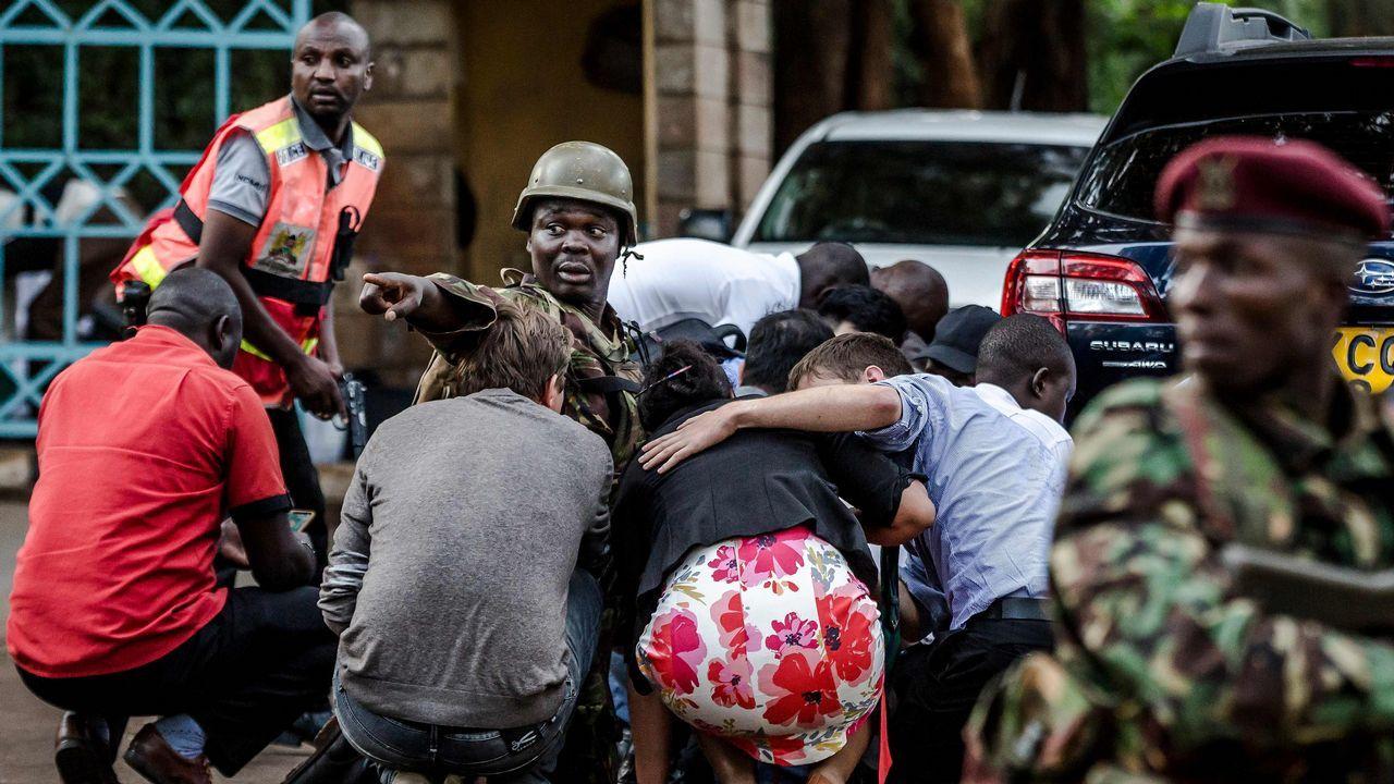 Agentes de seguridad protegen a un grupo de civiles en el exterior de las instalaciones