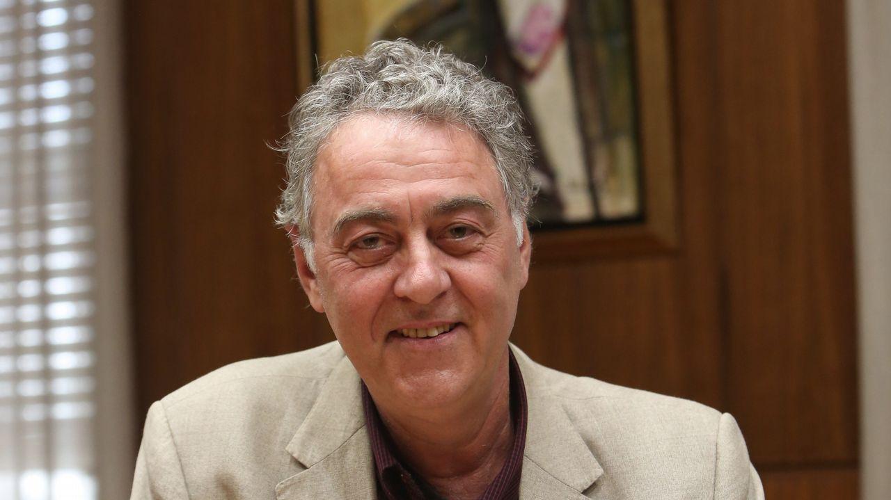 O pintor Antón Lamazares con obras da exposición «Flor Novoneyra» en Santiago