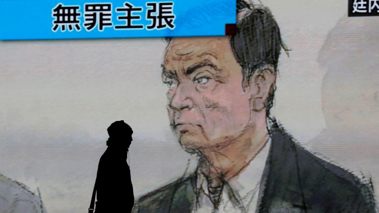 Peatones caminando junto a una pantalla con el retrato del expresidente de Nissan, Carlos Ghosn