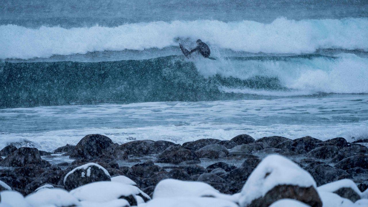 Una surfera toma una ola en plena nevada en la costa de Noruega