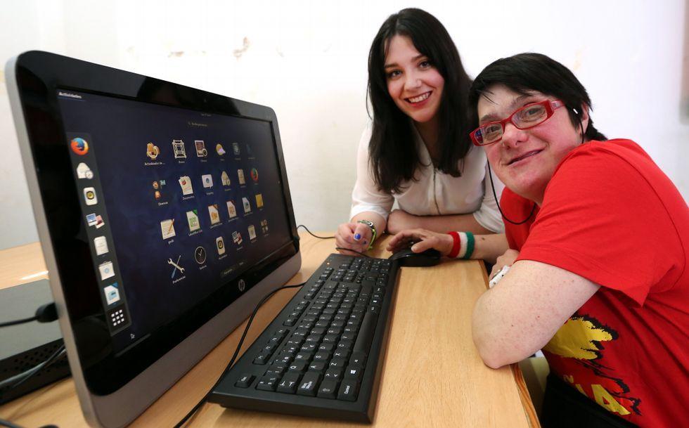 <span lang= gl >Montse Rebullido, fronte ao ordenador que empregan nas sesións, axudada por Sandra Riveiro. </span>