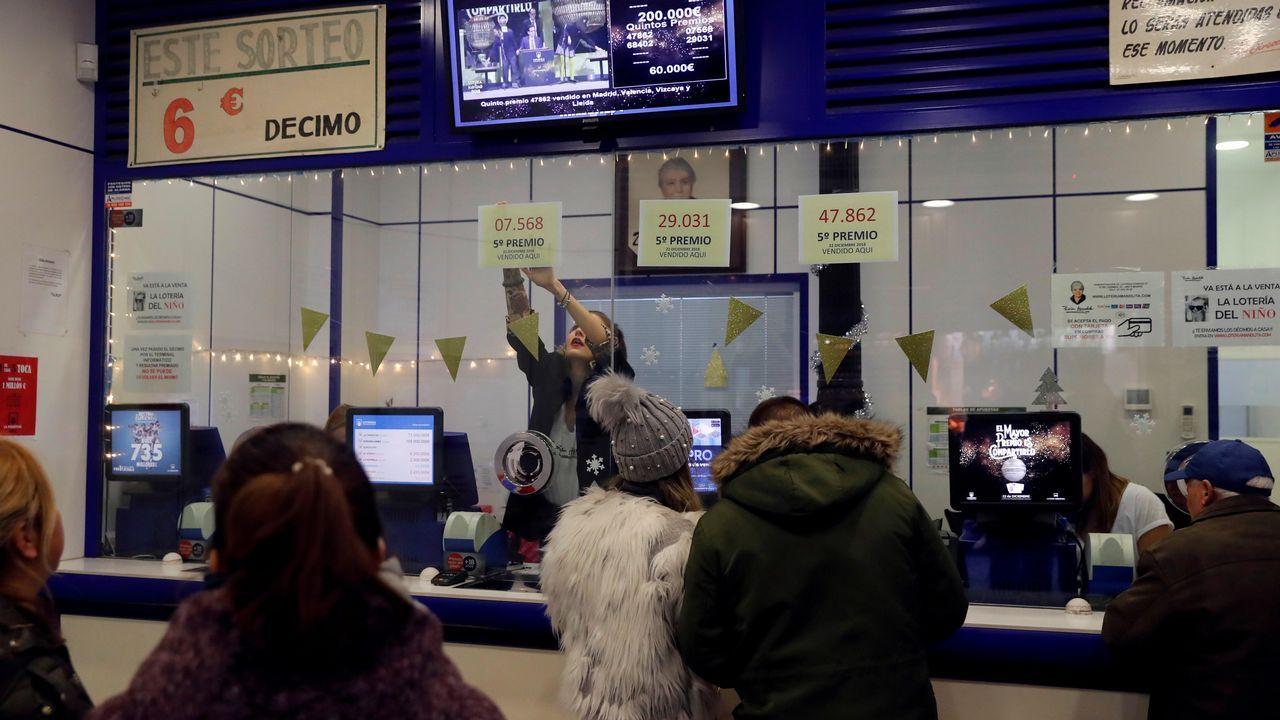 Una empleada de la administración de Loteria de «Doña Manolita» en la madrileña calle Carmen, 22, coloca los números correspondientes a los tres quintos premios
