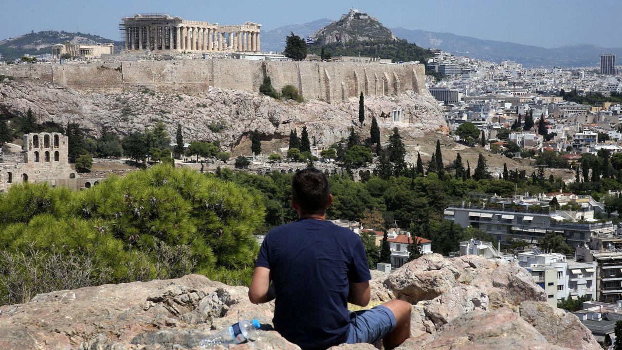 Un turista contempla las vistas de la colina donde se sitúa la Acrópolis de Atenas
