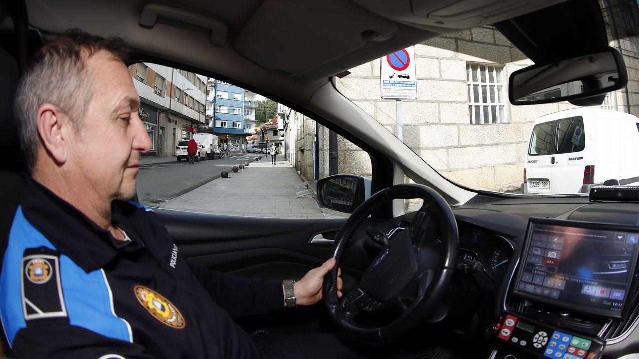 Un policía local gestiona el sistema que localiza y multa a los vehículos que exceden el tiempo de la ORA en Ribeira