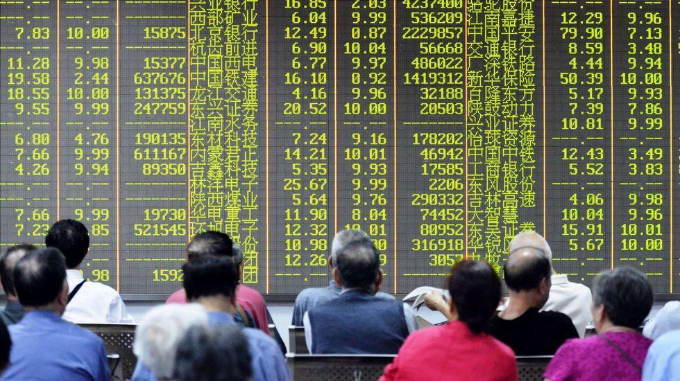 Ciudadanos chinos observan preocupados las caídas que reflejan las pantallas.