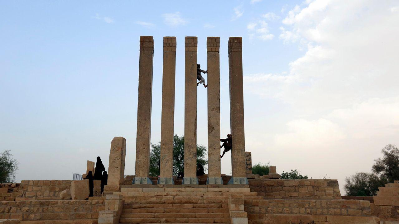 .Dos hombres escalan por las columnas de los restos del Palacio de la Reina de Saba en Marib (Yemen). El palacio fue construido durante el reinado de la Reina de Saba en el siglo X a.C. y permaneció enterrado bajo las dunas del desierto hasta que fue descubierto en 1988 durante unas excavaciones arqueológicas