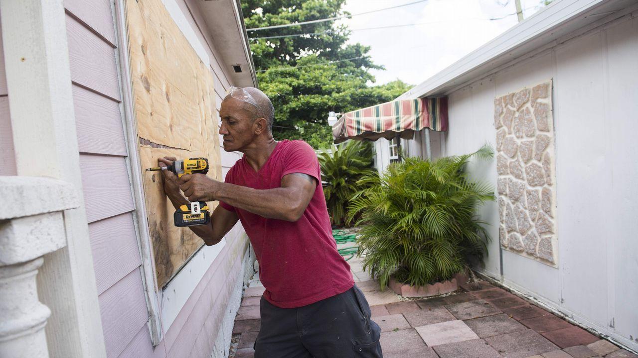 Un hombre tapa las ventanas de su hogar con tablones contrachapados.